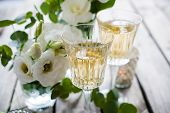 stock photo of wedding table decor  - Two glasses of champagne and white flowers - JPG