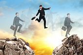 pic of gap  - Image of young businessman jumping over gap at the sunset - JPG