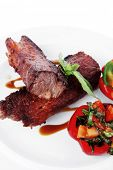foto of braai  - fresh red beef meat steak barbecue garnished vegetable salad and basil  in half of pepper bell on white plate isolated over white background - JPG