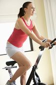stock photo of exercise bike  - Young Woman On Exercise Bike - JPG