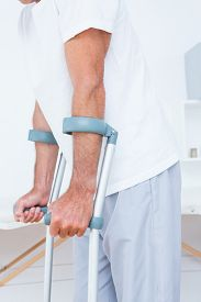 picture of crutch  - Patient standing with crutch in medical office - JPG