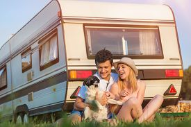 stock photo of camper  - Beautiful young couple in front of a camper van on a summer day - JPG