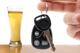 picture of designated driver  - Drunk driving conceptual image with a hand holding some car keys and a glass of beer in the background - JPG