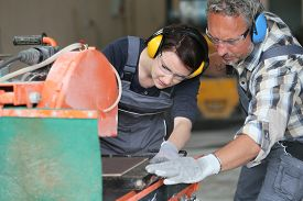 stock photo of thermal  - Tiler showing apprentice how to use thermal grinder - JPG