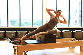 stock photo of leotard  - Healthy Brunette Woman Wearing Leotard and Practicing Pilates in Exercise Studio - JPG
