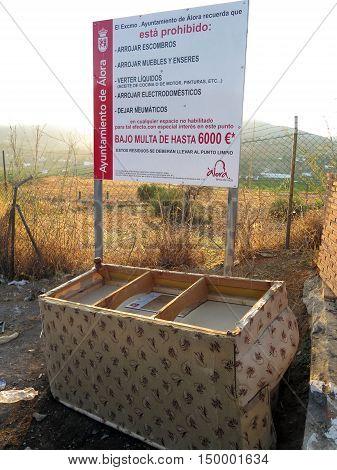 Alora Spain - September 27 2016 - Settee dumped underneath warning sign regarding fly tipping