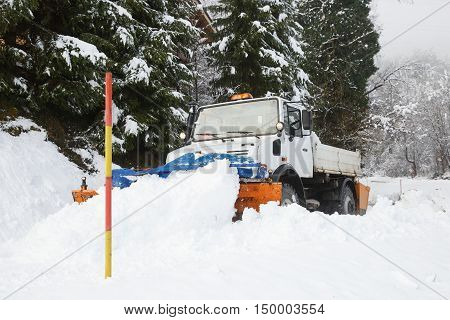 Snow plough making its way through the snowy country road clearing snow after blizzard with snow road marker pole in the foreground. Professional winter services road conditions in winter concept.