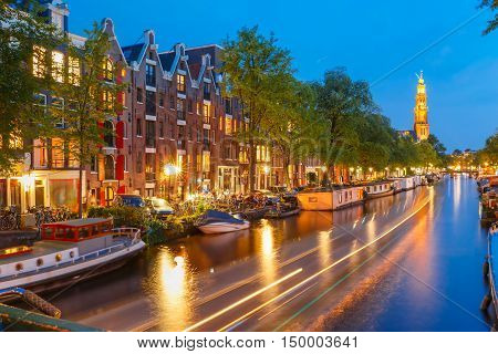 Night city view of Amsterdam canal Prinsengracht with houseboats and Westerkerk church and luminous track from the boat, Holland, Netherlands.