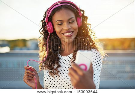 Attractive woman listening to music on her mobile on a set of trendy pink headphones smiling happily as she checks the screen of her phone