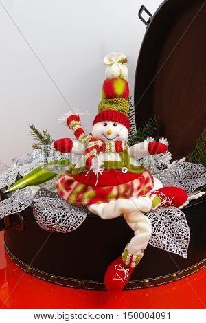 Funny snowman sits on vintage brown coffer with white Christmas tree decoration copy space