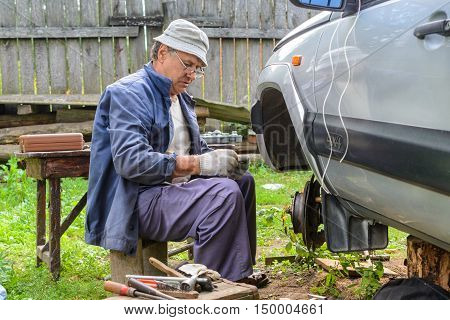 Elderly man repairing the front hub wheels. car repair at home.