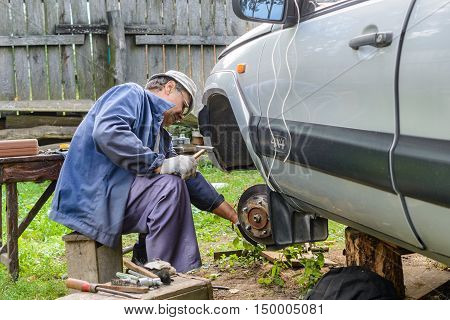 Senior mechanic replaces the vehicle's front wheel. vehicle repair in the absence of the service station.