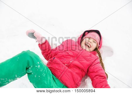 Playful girl with braids playing in snow making a snow angel having fun being active and happy with the first snow. Natural lifestyle and free childhood concept with copy space.