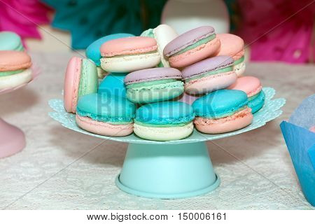 Sweet colorful macaroons in vase on the table. Candy bar backgroud