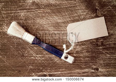 Paint brush with blank tag on wooden background