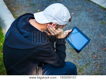 Pensive Teenager with Tablet Computer sit outdoor