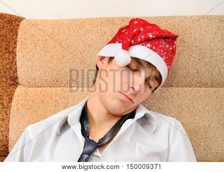 Tired Young Man in Santa Hat sleep on the Sofa at the Home