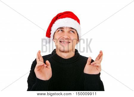 Young Man in Santa Hat crossing his Fingers Isolated on the White Background