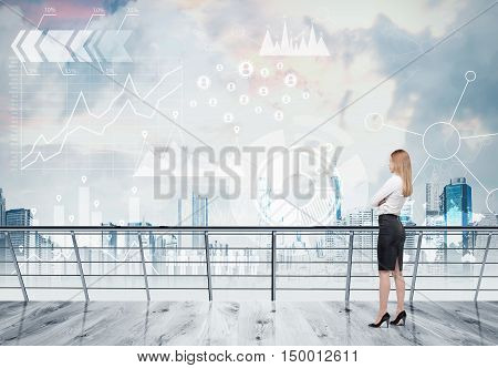 Side view of blond girl looking at transparent graphs in the sky. Concept of the future is now. Double exposure