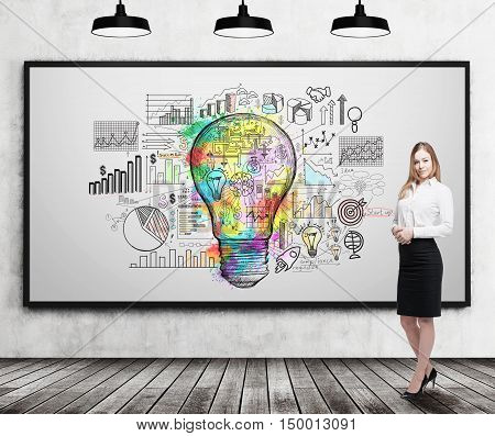 Smiling blond businesswoman standing near whiteboard with bright light bulb on it. Concept of creativity in business