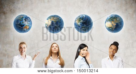 Group of women standing near concrete wall with Earth globes hanging above their heads. Concept of women's position in society in different countries