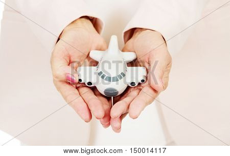 Elderly woman holding a toy plane on open plams