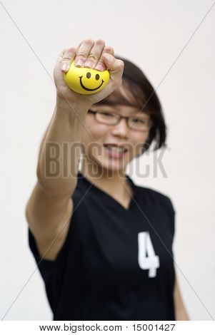 Asian  lady squeezing yellow happy ball