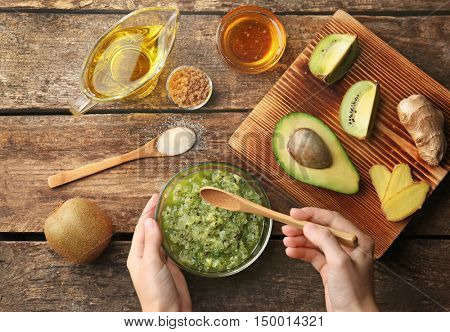 Female hand making nourishing facial mask with natural ingredients on wooden background