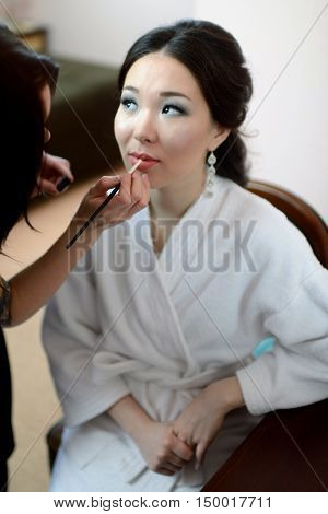 Wedding Makeup Artist Making A Make Up For Bride. Beautiful Sexy Model Girl Indoors. Beauty Woman Wi