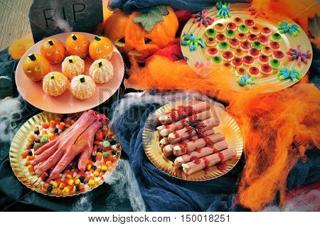 some plates with Halloween food such as candies scary fingers or mandarines as pumpkins with different scary ornaments as spiders cobwebs or a tombstone