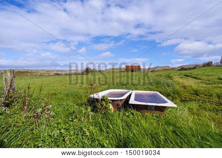 Rural landscape on Isle of Skye Scotland with two rusty enamel baths used for water for cattle in a grassy field and abandoned derelict stone barn