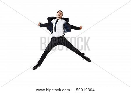 Young successful businessman in suit rejoising, jumping over white background. Copy space.