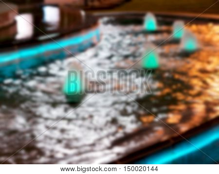 Blurred Bright Jet Water Fountain. City Fountain In The Park, Lit Lamps. Blurred Bokeh Basic Backgro