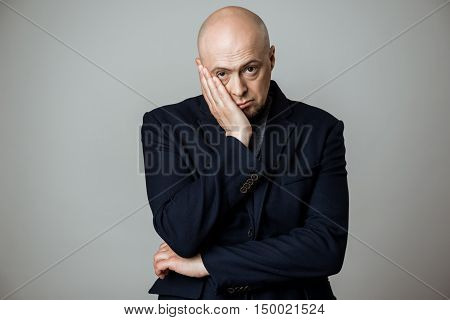 Young upset businessman grab his face, looking at camera over beige background. Copy space.