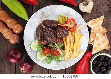 Turkish kofta kebab, minced meat skewer with salad and french fries