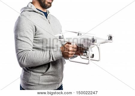 Unrecognizable man in gray sweatshirt holding drone with camera. Studio shot on white background, isolated.