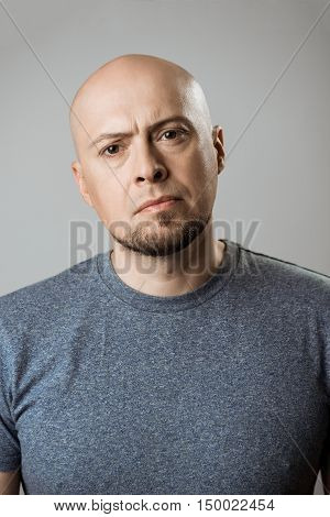 Displeased upset man looking at camera over beige background. Copy space.