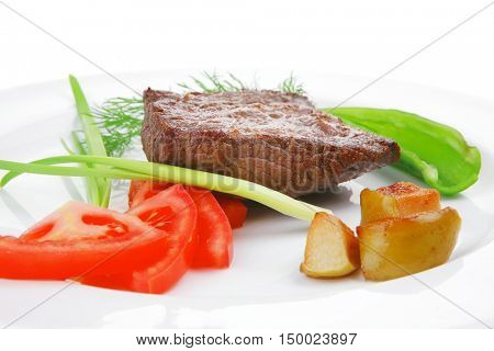 meat savory : grilled beef fillet mignon on white plate with tomatoes apples and pepper isolated over white background