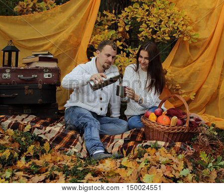 married couple in the autumn wood on a picnic give from a thermos some tea in a cup