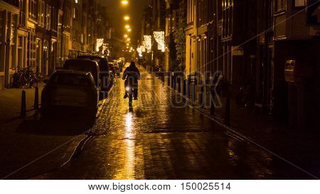 A bicyclist is silhouetted by street lights on a rainy evening in the Amsterdam city center.