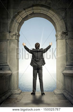 Businessman standing with arms raised in the arch of the ancient buildings in the sun.