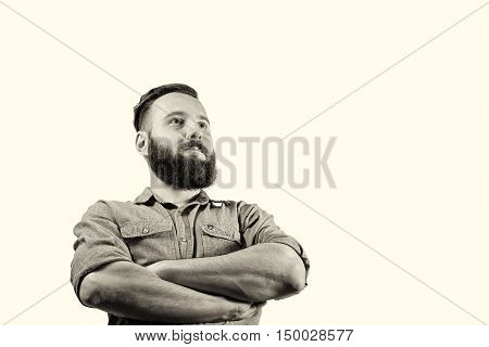 Black and white half-length portrait of a bearded man on a toned isolated background. The guy looks in front of him with his arms crossed.
