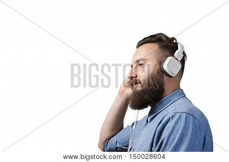 A bearded man in a denim shirt listens to music through white headphones. Image on white isolated background with a space for your text or desing.