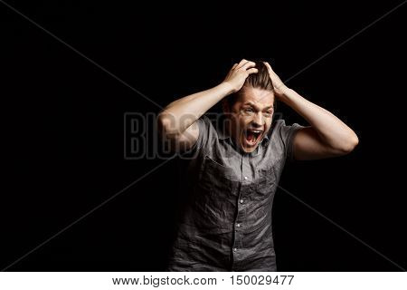 Dissapointed young handsome man grab his head, shouting over black background. Copy space.