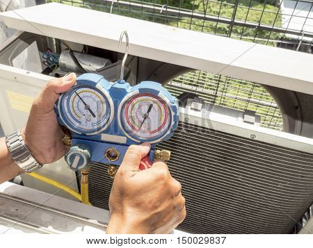 Single man hold manometer Measure equipment of Air Conditioner on his hand under sunlight in the balcony