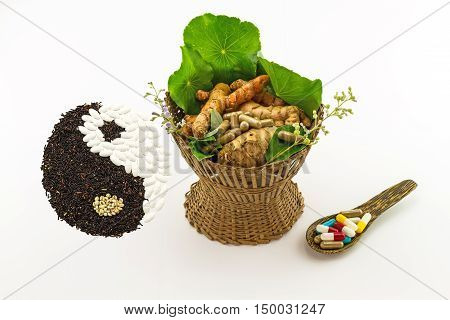 Assorted of herbal in brown bamboo basket and colorful pills in wooden spoon and black rice and white pill forming a yin yang symbol indicate blending of herb and medicine on white background
