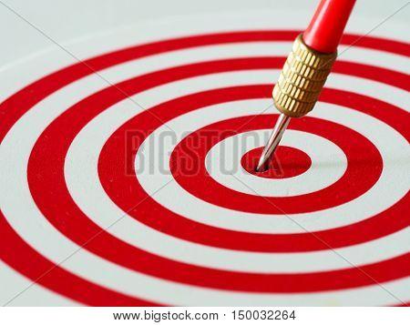 Red bullseye dart arrow hitting target center of dartboard. Concept of success target goal achievement. (selective focus)