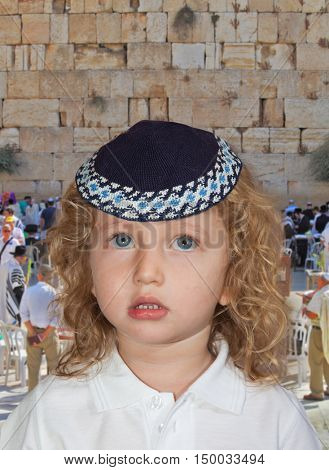JERUSALEM, ISRAEL - OCTOBER 12, 2014: Morning autumn Sukkot. Cute little boy with long blond curls and blue eyes in knitted skullcap. He stands at the main Jewish shrine - Western Wall of Temple