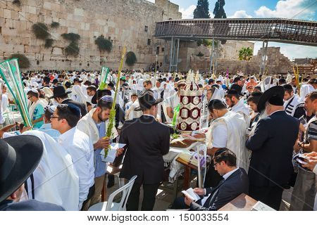 JERUSALEM, ISRAEL - OCTOBER 12, 2014:  The area in front of Western Wall of Temple filled with people. The Jews of ritual tallit worship with prayer books in their hands.  Morning autumn Sukkot