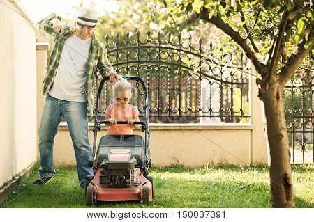 Little girl is mowing the lawn with her father.